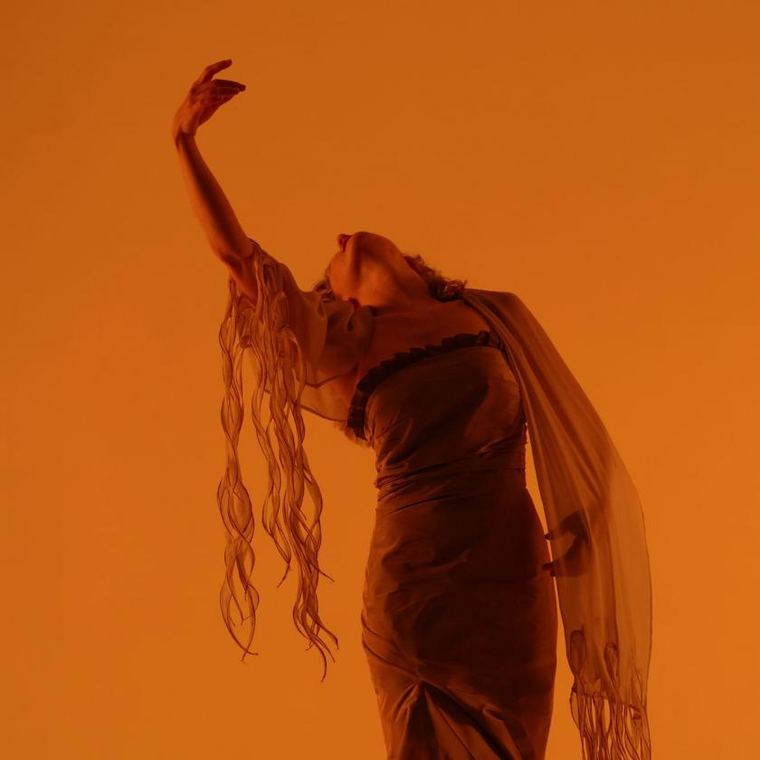 Suzie LeBlanc dancing over an orange background