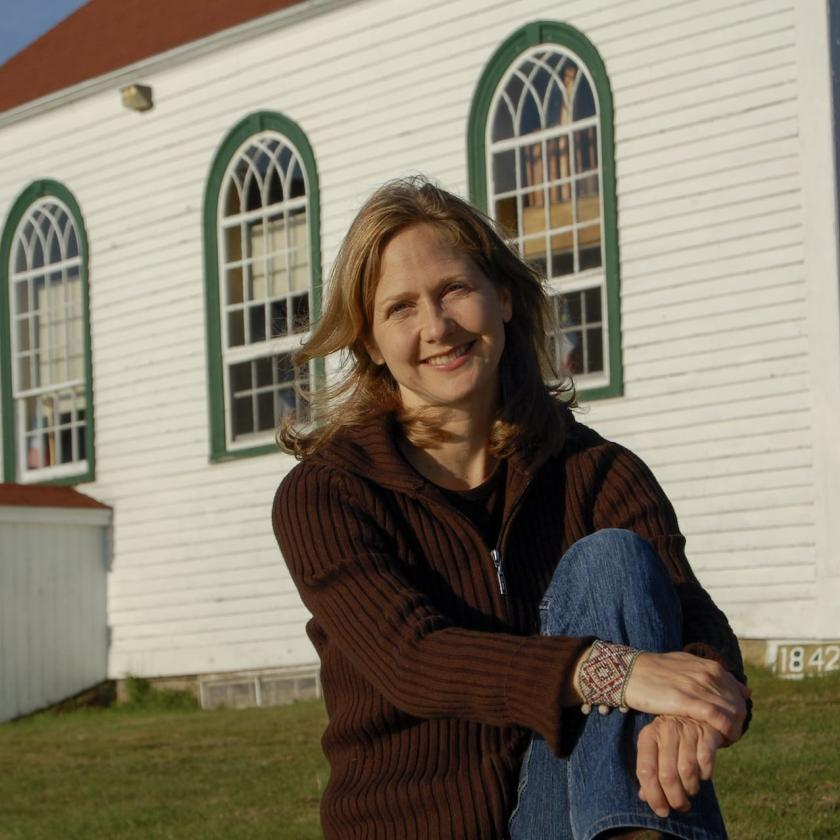Suzie LeBlanc outdoors in front of a small wooden church